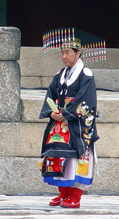 A male-presenting person in late middle age wearing a dark square hat with a row of colorful ornaments hanging from the front and back brim and an dark blue-grey robe with embroidery and a red panel in front, with a white robe underneath and red boots. He holds a long white piece of wood at waist level, pointing it upward.