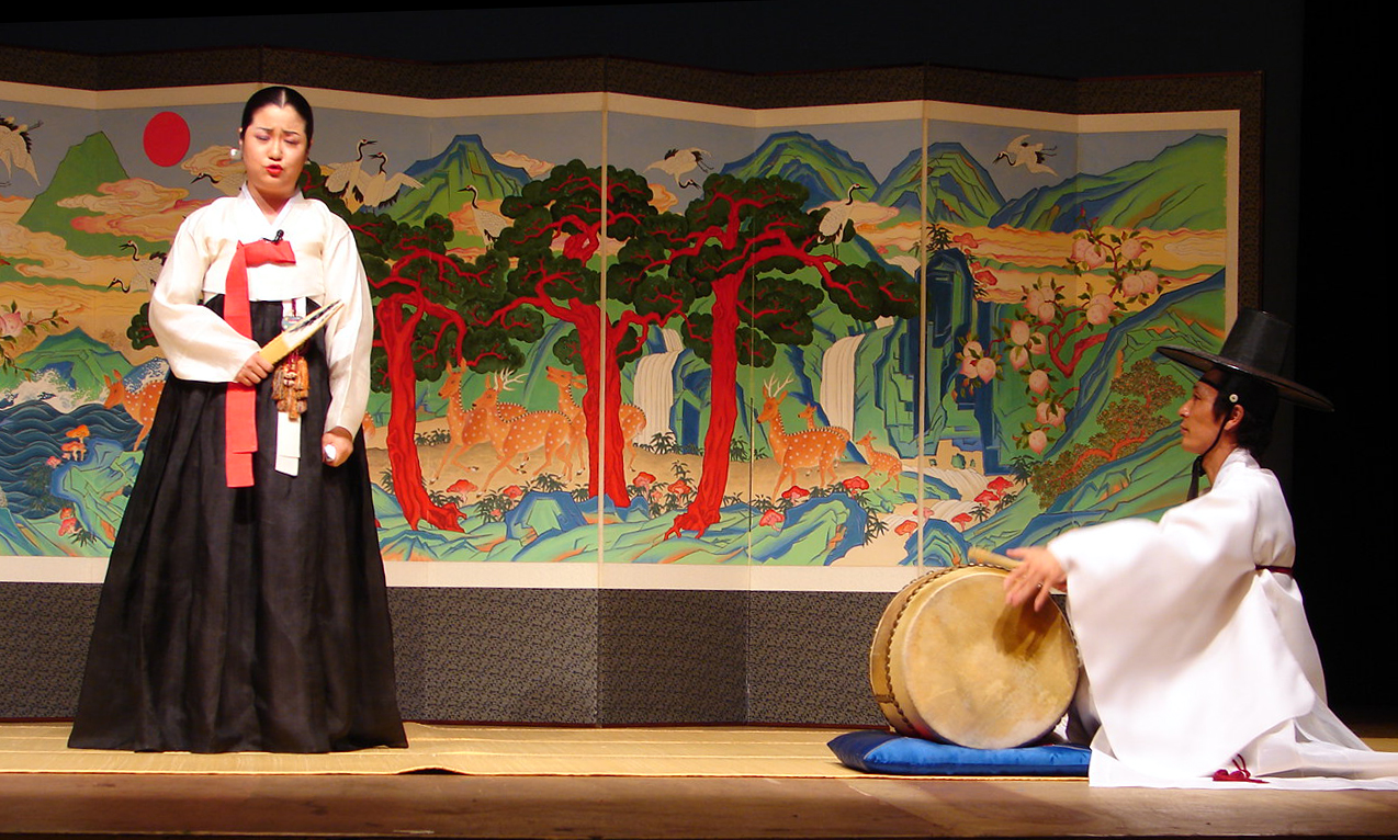 A female-presenting person in traditional Korean hanbok holding a closed fan stands before a painted screen, with a male-presenting person in hanbok sitting off to the right playing a drum.